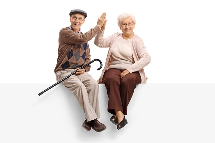 A senior couple sitting on a bench give each other a high five.