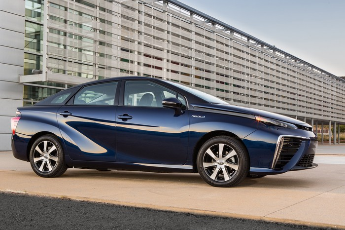 A dark blue Toyota Mirai sedan outside an office building.