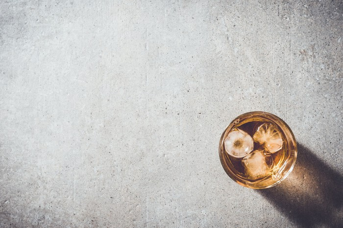 An overhead view of a glass of whiskey sitting on a table.