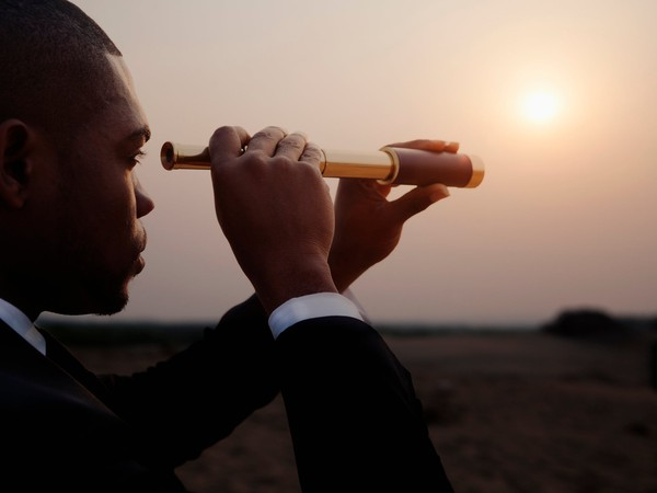 man in business suit looking through telescope toward horizon long term future POC