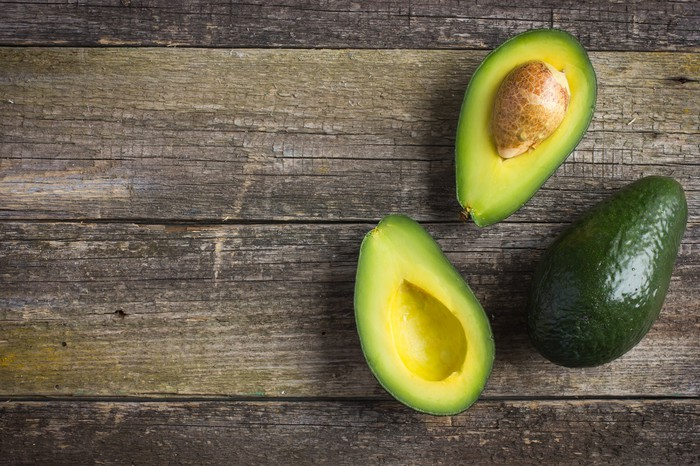An overhead view of avocados sitting on a wooden table.