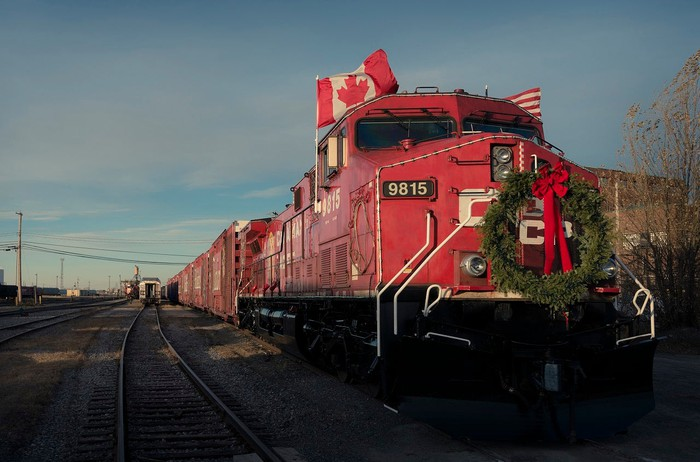 Train led by red locomotive with Canadian and American flags and a green wreath with red bow.