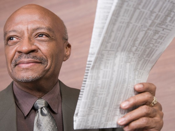 Senior businessman holding newspaper with stock listings