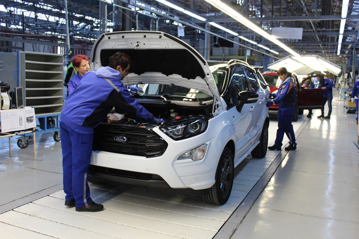 Workers attend to a white Ford EcoSport, a small SUV, on a factory assembly line.