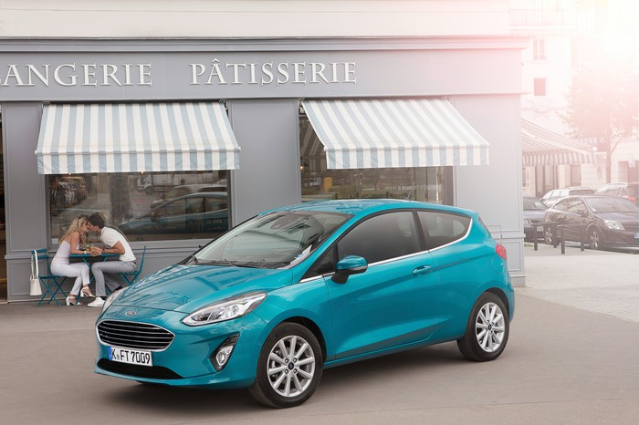 A teal two-door Ford Fiesta hatchback is parked in front of a French bakery.