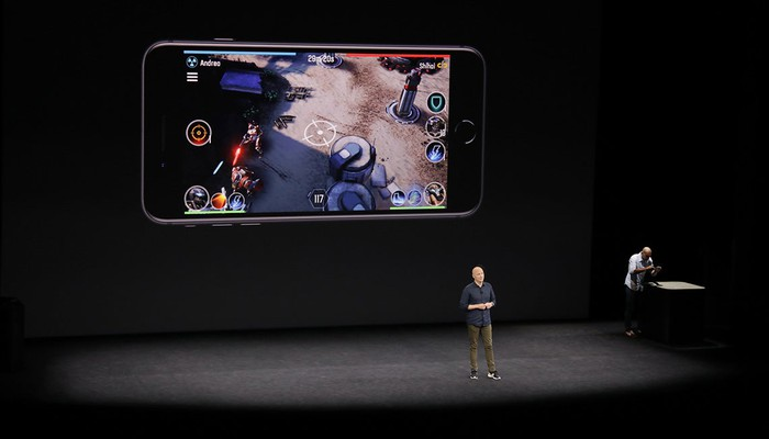 A person on stage with an iPhone playing a 3D game projected on the screen behind him.