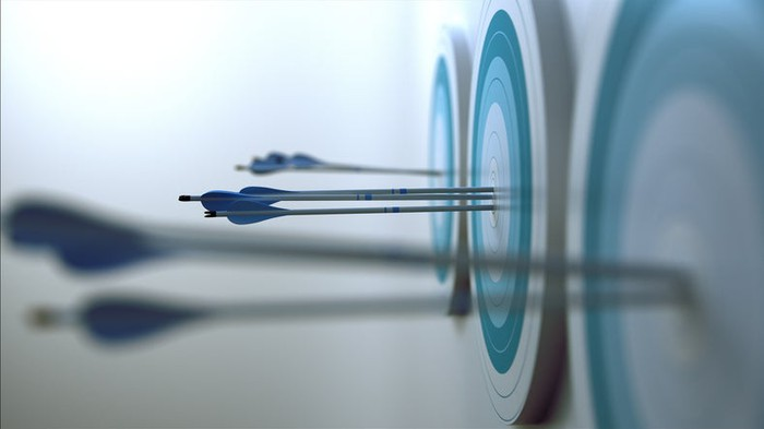 Blue darts hitting bull's-eyes on three blue dartboards.