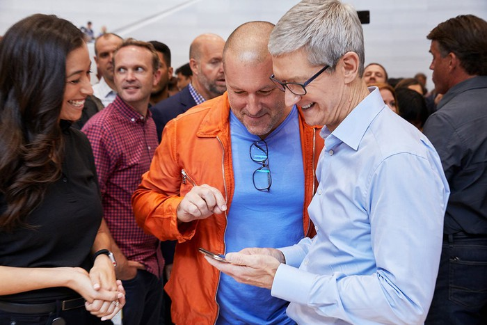 Apple CEO Tim Cook and Apple chief designer Jonathan Ive looking at an iPhone, surrounded by a crowd of people