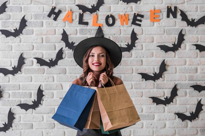 A woman carries bags while wearing a witches' hat standing in fron of a wall decorated with bats.