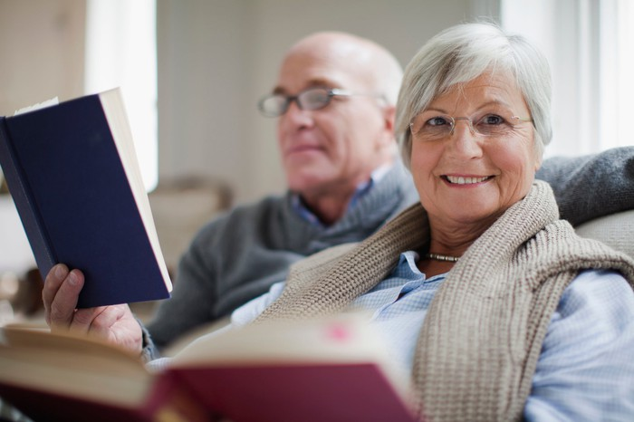 senior man and woman sitting on couch reading books