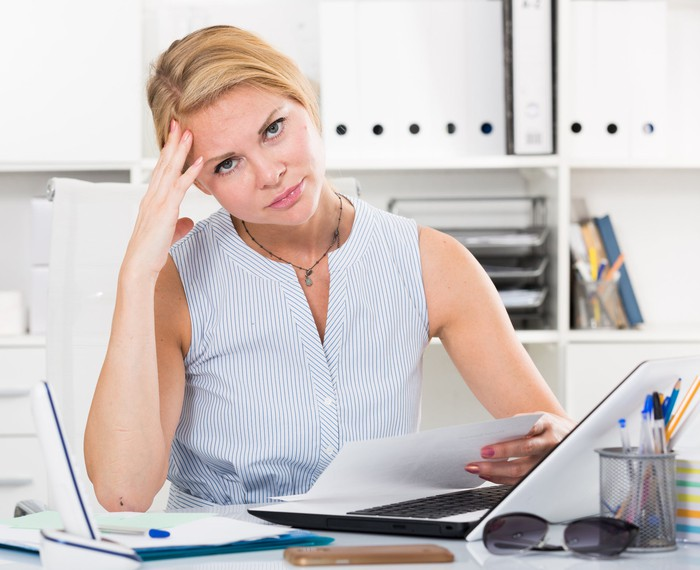 Woman looking sheepish at her desk, holding her head