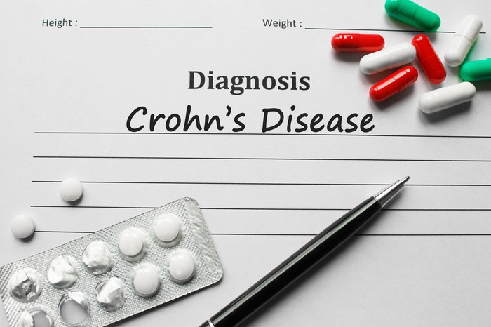 "Pills and pen on a paper that reads ""Diagnosis: Crohn's disease"""