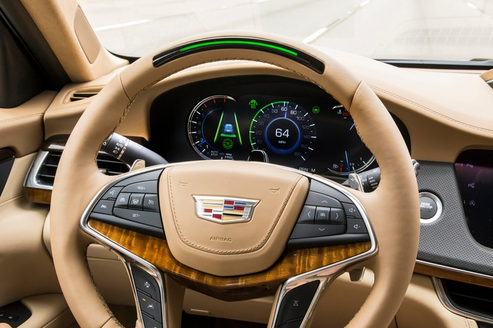 A view of a Cadillac CT6's steering wheel and instrument cluster, showing the Super Cruise light in the wheel's rim.
