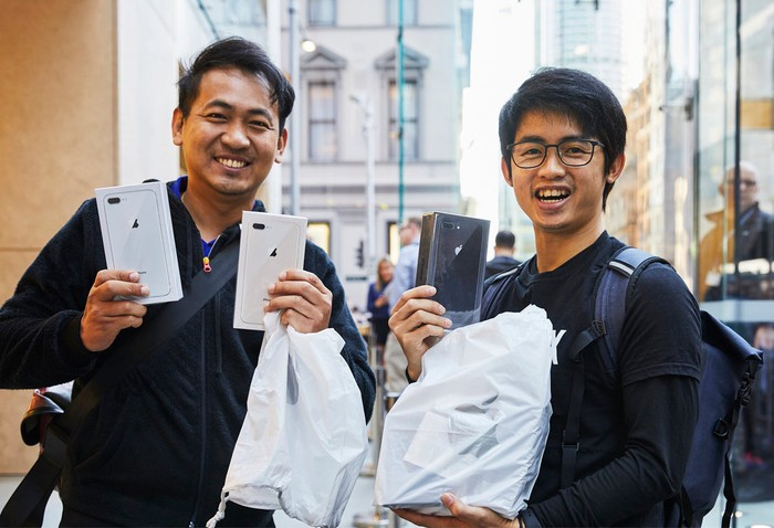 Two customers holding up new iPhones on launch day
