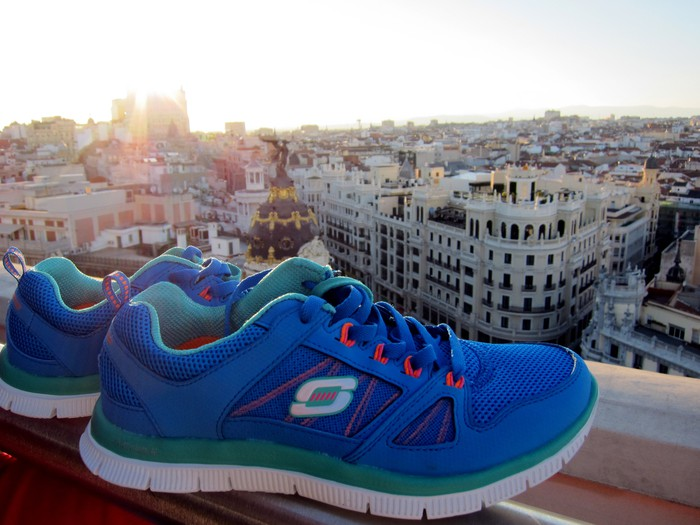 A pair of blue Skechers sneakers overlooking a city in Spain.