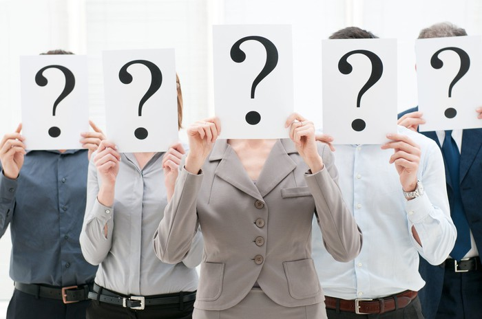 five businesspeople, each holding a white paper in front of their face with a big question mark on it