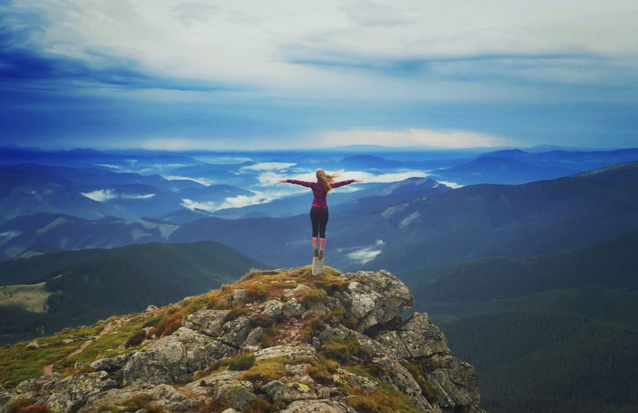 young woman stands  with arms outstretched on top of a mountain