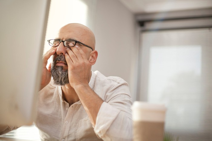 Man rubbing his eyes in front of a computer