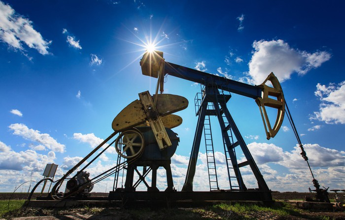 An oil pump under partly cloudy skies with the sun shining brightly