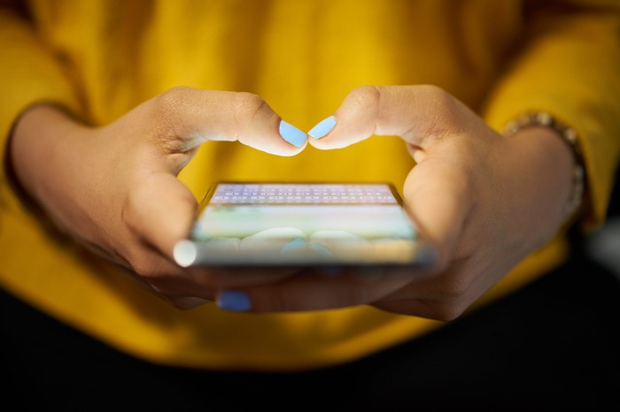 A woman's hands texting on an illuminated smartphone screen.