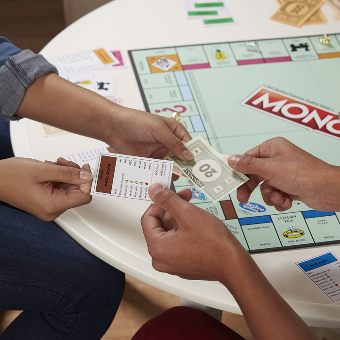 Monopoly game player exchanging a property card for cash.