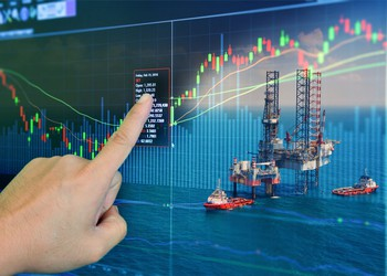 An investor pointing at a stock screen with an oil drilling rig in the background.
