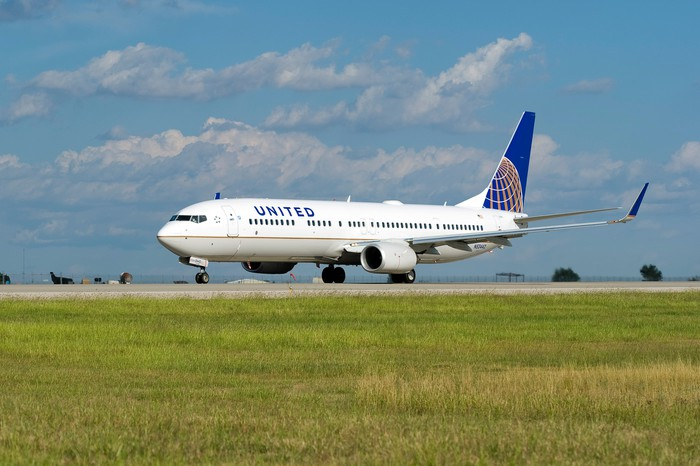 A United Airlines plane on the ground, with clouds in the background