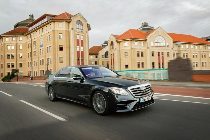 The Mercedes-Benz S Class Salon in the color black is shown speeding on a road with buildings in the background.