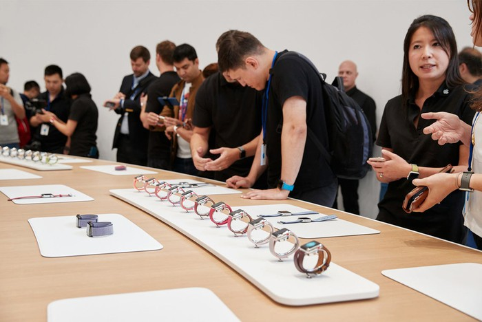 People standing in front of a table with Apple Watches lined up on it.
