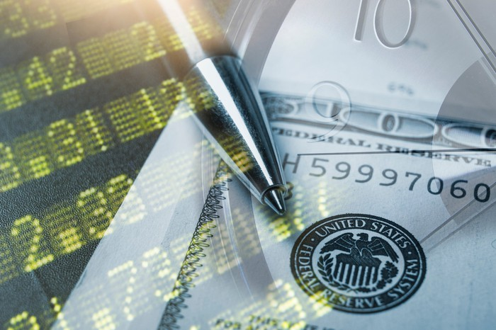 Stock index board, $100 bill, and clock all superimposed on top of each other.