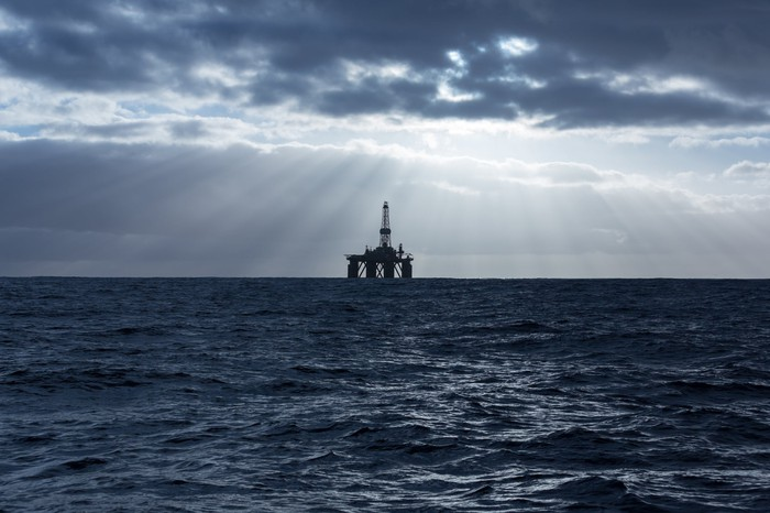 Offshore drilling rig with dark clouds overhead but the sun still shining through.