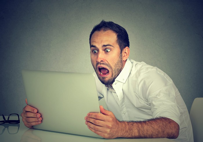 A man clutches a tablet and looks at it with an open-mouthed, terrified expression.