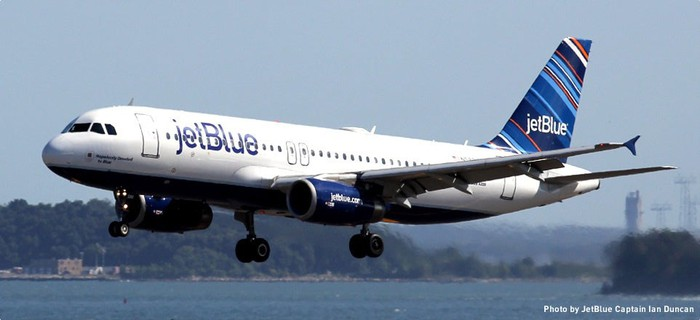 A JetBlue Airways plane about to land, with water in the background