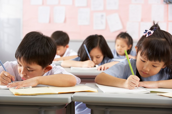Chinese students working on schoolwork in a classroom.