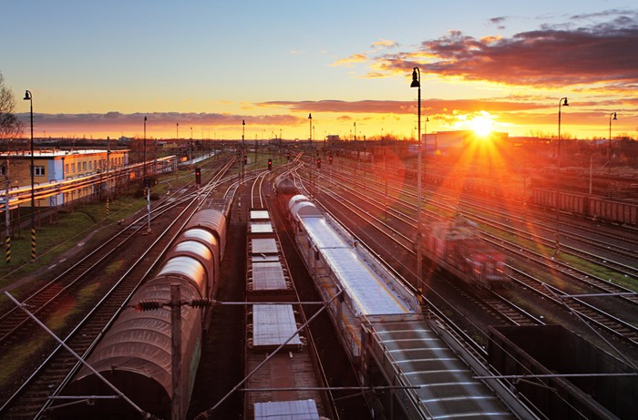 Freight trains at a station with the sun setting in the background.
