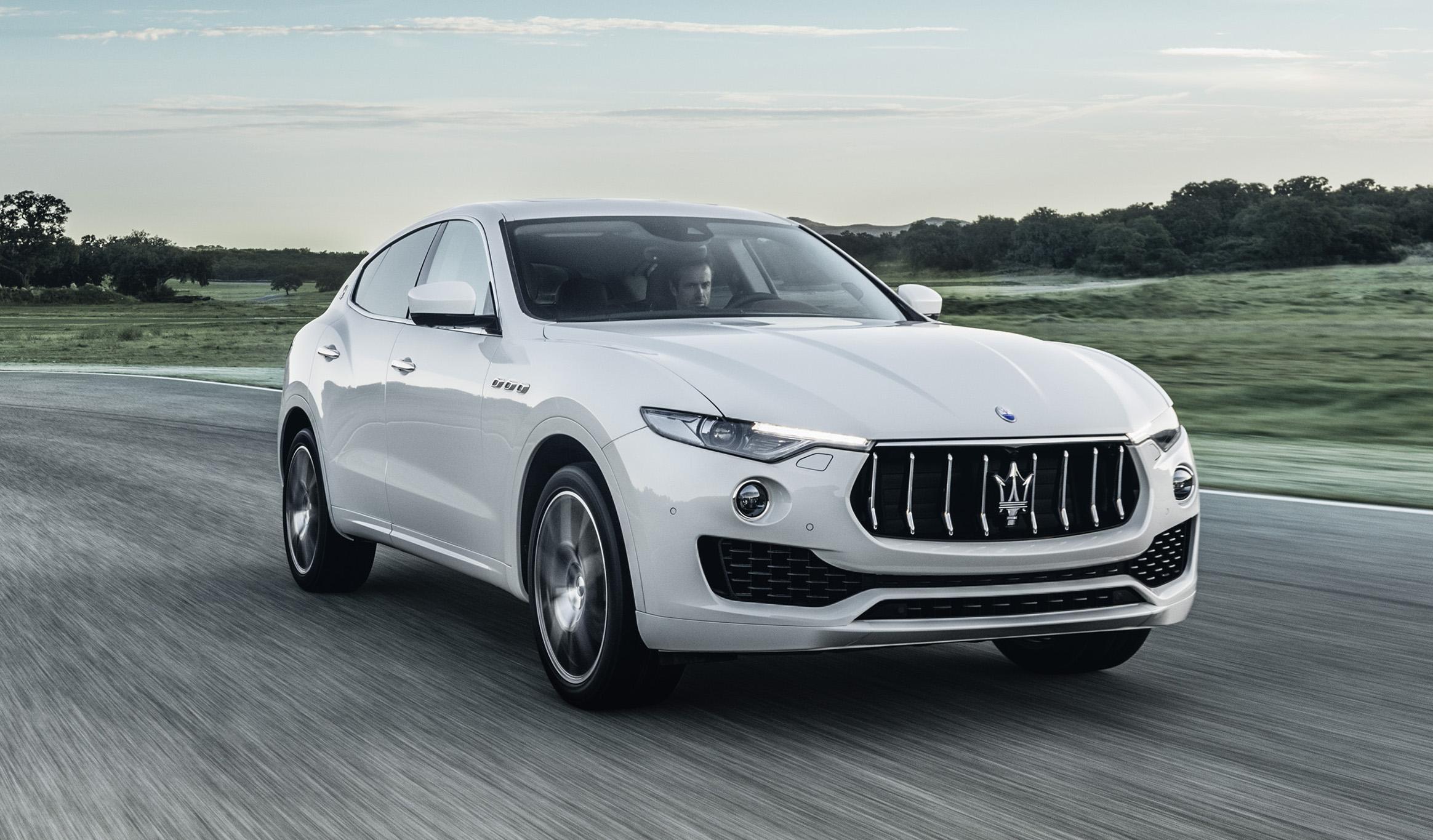 A white Maserati Levante, a midsize luxury SUV, on a country road.