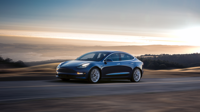 A blue Tesla Model 3 driving on a scenic road