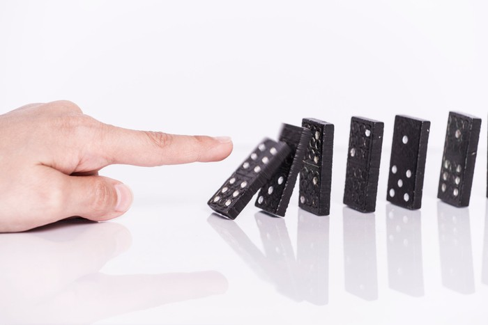 Dominoes being pushed over