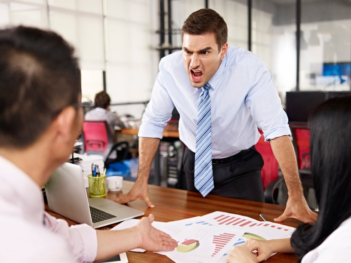 A man in shirt and tie leans on a table and yells across it in menacing fashion at others.