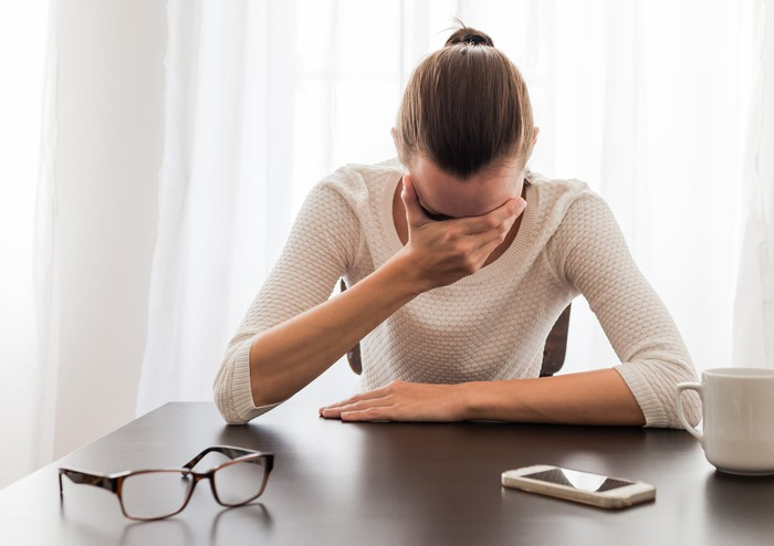 A woman sits at a table, glasses and phone lying in front of her, as she holds her face in her hand, appearing to be crying.