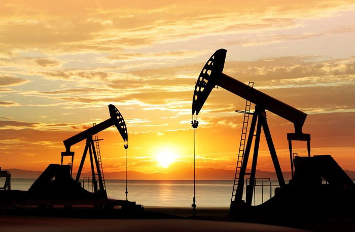 Oil drilling rigs in operation with the sunset in the background.