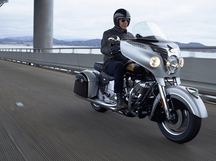 A man riding a Polaris Indian motorcycle over a bridge.