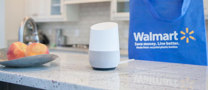 A Google Home smart speaker and a Walmart shopping bag on a kitchen counter.