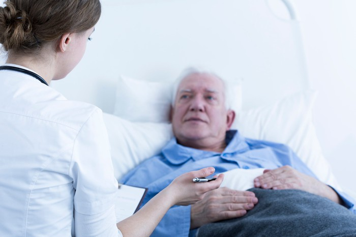 Senior male in bed talking to a woman