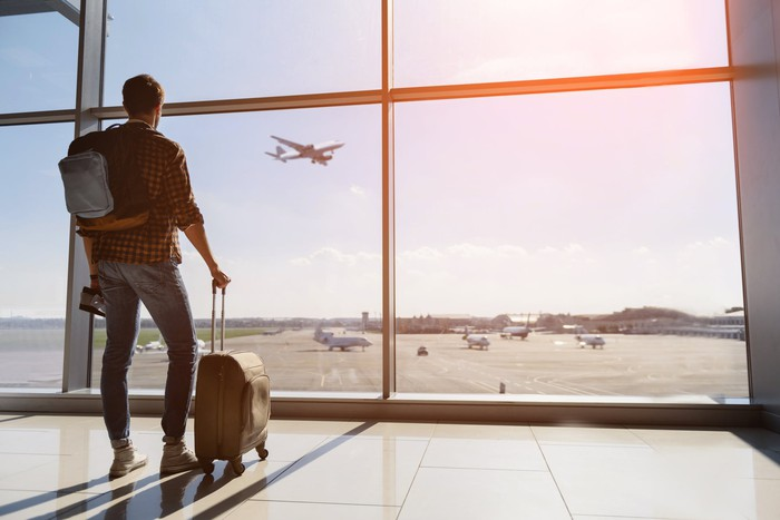 A young man stands in an airport and watches a plane takeoff.