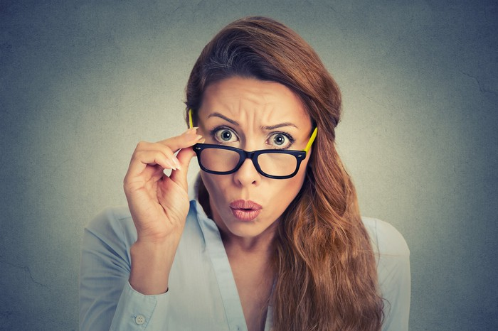 Woman looking surprised, peering at camera as she takes off her glasses