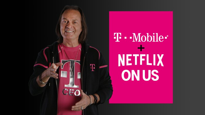 "T-Mobile CEO John Legere standing next to a sign that says ""T-Mobile plus Netflix on us"""