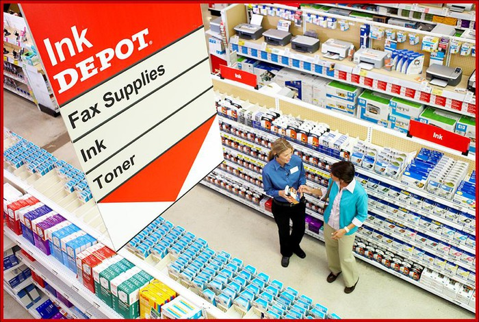 An overhead view of an employee and a customer talking in the Office Depot ink section.