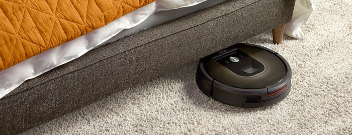 A Roomba vacuum cleaner going under a piece of furniture in a carpeted room.