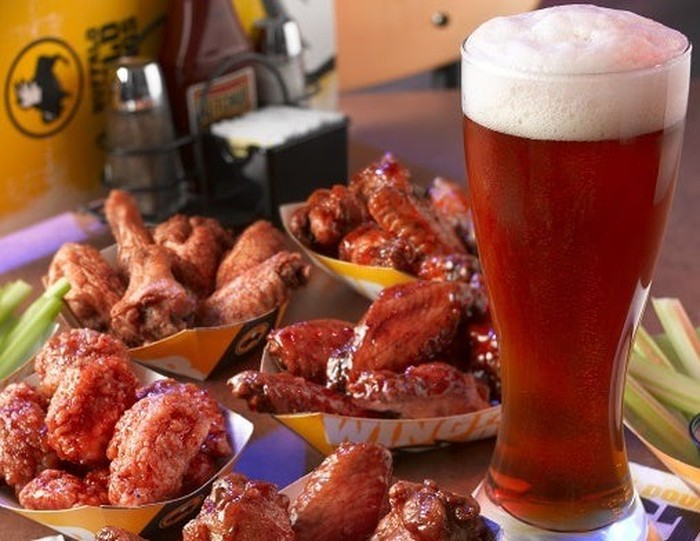 A large glass of beer next to various Buffalo Wild Wings traditional wings.